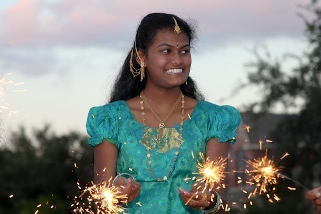 Girl celebrates Diwali with smiles and sparklers